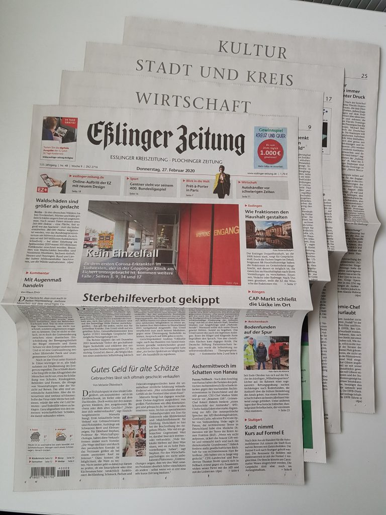 Zeitung im Vollformat mit hintereinander liegenden Büchern